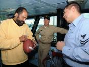 English: Pro Football Hall of Fame running back Franco Harris autographs a football for Yeoman 2nd Class David Lomeli during a tour of the aircraft carrier USS George Washington (CVN 73). The four-time Super Bowl Champion with the Pittsburgh Steelers visi