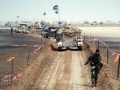 A column of M-113 armored personnel carriers and other military vehicles of the Royal Saudi Land Force travels along a channel cleared of mines during Operation Desert Storm.