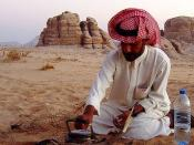 A young Bedouin man called 'Nasser' lighting a fire in Wadi Rum, Jordan