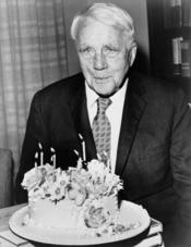 Robert Frost poses with his birthday cake on his 85th birthday