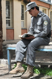 Afghan National Police Officer reading in his off time