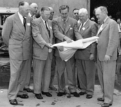 Walt Disney shows Disneyland plans to Orange County officials in December 1954. The men in the front row (left to right) are Anaheim Mayor Charles Pearson, Orange County Supervisor Willis Warner, Walt Disney, Supervisor Willard Smith, and Orange County Pl