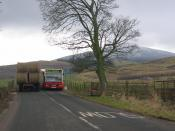 English: Thankerton traffic jam. Thankerton is bypassed, but that does not stop the chaos when the bus from Biggar cannot get past a parked tractor. Tinto in the distance. (A driveby taken during the long wait for the bus driver to get the courage to sque