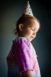 English: Two-year-old girl in traditional American birthday hat.