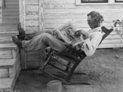 A Farmer Reading His Paper. Photographed by George W. Ackerman, Coryell County, Texas, September 1931.