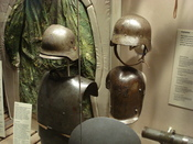 English: WWI German body armor, double-reinforced steel helmet, and arm shield on display at the Canadian War Museum with WWI sniper camouflage in background.