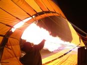 Hot air balloon being inflated by its propane burners prior to a dawn launch.