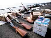 A Remington 870 Wingmaster 12-gauge shotgun, two Remington 1100 12-gauge shotguns, boxes of shells and clay targets are laid out on the fantail of the battleship USS MISSOURI (BB-63) in preparation for skeet shooting practice.