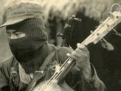 A member of the Ejército Zapatista de Liberación Nacional, playing a crude 3 string slide guitar in Chiapas, Mexico
