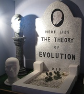 English: Photo of a diorama showing a mock grave for evolution on display at the genesis expo.
