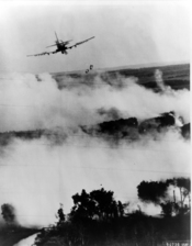 Two napalm bombs tumble from a Vietnamese Air Force A-1E Skyraider over a burning Viet Cong hideout near Cantho, South Viet Nam.