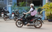 English: A woman riding a motorcycle in Dương Đông, Phú Quốc, South Vietnam. She wears long gloves and a hat to protect her skin from the sun, despite the heat (around 30°C).