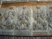 Temple carving at Hoysaleswara temple representing the Trimurti: Brahma, Shiva and Vishnu.