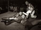 English: A wrestling match performance in Sikeston, Missouri, May 1938. Two wrestlers grapple while the referee (in white, right) looks on. The bearded wrestler is known as Big Tom Towers. Description on photo: