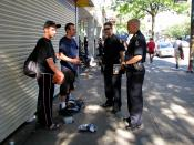 English: Vancouver Police officers ordering two sidewalk vendors to leave the area. One of the youths took exception to the photograph, whereupon one of the officers very clearly stated to him that it was fully permissible under Canadian law to record suc