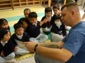 US Navy 040308-N-3614M-001 Master Chief Information Systems Technician Don Acker, of Augusta, Kan., reads to children at a daycare in Hong Kong