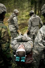 Soldiers carry Pfc. Kristopher Sirnell between obstacles Jan.23 during a practice exercise for the Expert Field Medical Badge (EFMB). U.S. Army photo by Phil Sussman Soldiers overcome grueling test of skill to earn coveted Expert Field Medical Badge