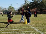 Sailors help children at an athletics event.
