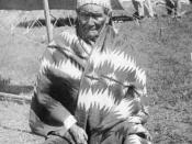 Geronimo, a Native American (Chiricahua Apache) man, a U. S. prisoner, poses outdoors near a group of tents. He wears a woven blanket and beaded cap. He has defended his people from the harm of the U.S land takeover.