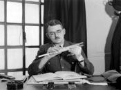Frank Whittle adjusts a slide rule while seated at his desk at the Ministry of Aircraft Production.