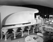 English: Black and white photo of an interior room with a counter and chairs. John F. Kennedy International Airport, New York