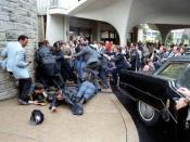 Chaos outside the Washington Hilton Hotel after the assassination attempt on President Reagan. James Brady and Thomas Delahanty lie wounded on the ground.