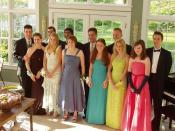 A typical gathering, with boys in tuxedos, and girls in dresses with corsages on their wrists.