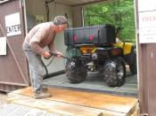 English: ATV rider using power wash station to clean his vehicle for a trail ride, to prevent the spread of invasive species from all-terrain vehicles.