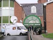 English: Tyrone County Hospital. I was passing the day that it was announced that this hospital was about to be replaced with another facility - a blow to the local community, camera men and reporters pictured outside with a van equipped with a satellite