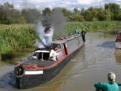 English: Steam powered narrowboat on the Oxford Canal A steam powered narrowboat on the Oxford Canal near Hillmorton just below locks 2 and 3. The steam whistle is blowing. Note the Rugby radio transmitter masts in the background.