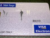 A Norwegian Visa Electron card issued by SpareBank1 Midt-Norge in 2006. A 1-krone coin is shown for scale. Sensitive numbers have been obscured. Picture taken and released into the public domain by User:Kallemax.
