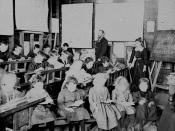 English: Interior of a school room at Postmans Ridge in the Helidon district, ca. 1902 Teachers and students in a classroom of wooden, tiered seats and benches. Some girls sit on a bench at the front reading while the other students are writing. The teach