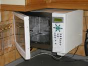 A wall-mounted combined microwave and fan-assisted oven, with the door open