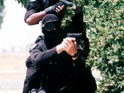 SRA Dave Orth (L) and SRA Clarence Tolliver (R), members of the 60th Security Police Squadron's Base Swat Team, Travis Air Force Base wearing black uniforms stand with M-9 pistols ready behind covering foliage. They are participating in a simulated hostag