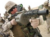 Staff Sgt. James C. Sanchez looks through the M2A1 reflex sight on the M-32 Multiple shot Grenade Launcher, an experimental six-round weapon that can deliver six 40 mm grenades in under three seconds. Marines are fielding the new rapid-fire weapon to troo