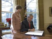 Laura Bush stands by President George W. Bush as he signs H.R. 6143, the Ryan White HIV/AIDS Treatment Modernization Act of 2006, in the Oval Office Tuesday, Dec. 19, 2006.