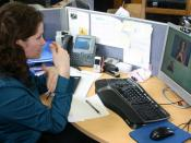 English: A Deaf, Hard-Of-Hearing or Speech-Impaired person at her workplace, communicating with a hearing person via a Video Interpreter (a Sign Language interpreter, shown on-screen), using a webcam and a videotelecommunications program on her computer.