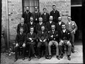 Group of fifteen men posed in front of large wall