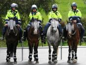 Australian mounted police officers on standby at a peaceful demonstration. Note the facial armour and reflective shin guards.