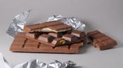 English: Brown swiss chocolate. The bar at the bottom is hazelnut chocolate, the bar in the middle contains pistachio nuts, the top bar is chocolate with a milk centre. Deutsch: Braune Schweizer Schokolade. Von unten nach oben: Haselnussschokolade, Pistaz