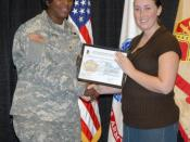 English: Col. Lillian Dixon, garrison commander, presents Jennifer Garrison, human resources assistant with the Directorate of Human Resources, with a certificate during the Employee of the Month award presentation Tuesday at the Solomon Center. Garrison