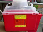 Sharps container (for safe disposal of hypodermic needles). Photographed at Street Outreach Services needle exchange, University District, Seattle, Washington. (The container would not normally be sitting on a chair; it was placed there to facilitate taki