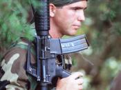 A Sea-Air-Land (SEAL) team member carries his Colt Commando assault rifle through the woods during a field training exercise.