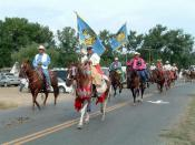 Pauline Small on horseback. She carries the flag of the Crow Tribe of Indians. As a tribal official, she is entitled to carry the flag during the Crow Fair Parade.