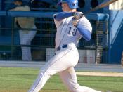 A batter follows through after swinging at a pitched ball.