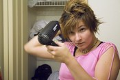English: Woman styling her hair with a blowdryer after a haircut.