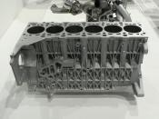 A modern passenger car engine block, integrating the crankcase and all cylinders. The cylinder head bolts to the deck surface at top. Many ribs and bosses can be seen on the side of the casting. This block is for a straight-six engine.