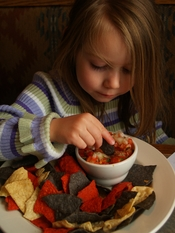 English: A young girl enjoys pico de gallo and American colored (red, white and blue) tortilla chips for the first time (technically) in Breckenridge, Colorado.