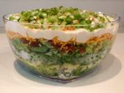 Seven-layer salad is an American dish that includes a colorful combination of seven layers of ingredients: iceberg lettuce, tomatoes, cucumbers, onions, sweet peas, hard boiled eggs, sharp cheddar cheese, and bacon pieces.The salad is topped with a mayonn