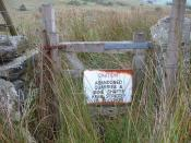 English: Dangerous ground. You have been warned! Sign on the overgrown path to Cae Amos.